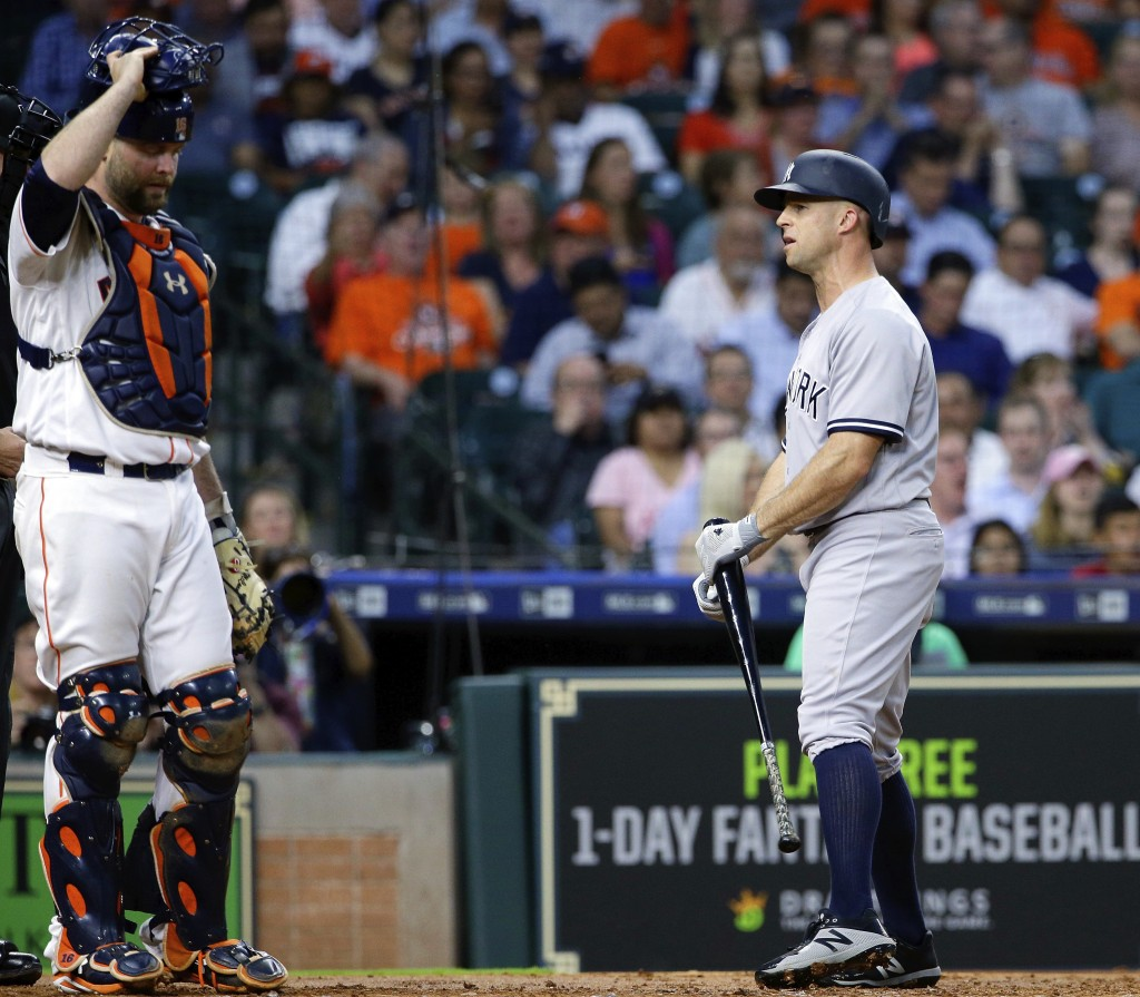 New York Yankees' left fielder Brett Gardner (11) has words with the umpire as he walks away from the plate after striking out as Houston Astros' catc...