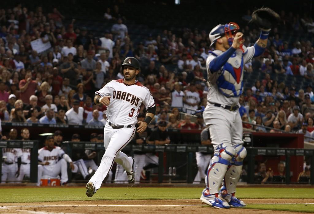 Arizona Diamondbacks' Daniel Descalso (3) scores a run as Los Angeles Dodgers catcher Yasmani Grandal, right, looks for a late throw to home plate dur...