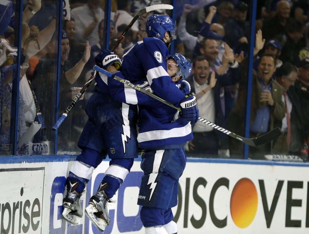 Tampa Bay Lightning center Tyler Johnson (9) gets lifted off the ice by left wing Ondrej Palat (18) after Johnson scored against the Boston Bruins dur...