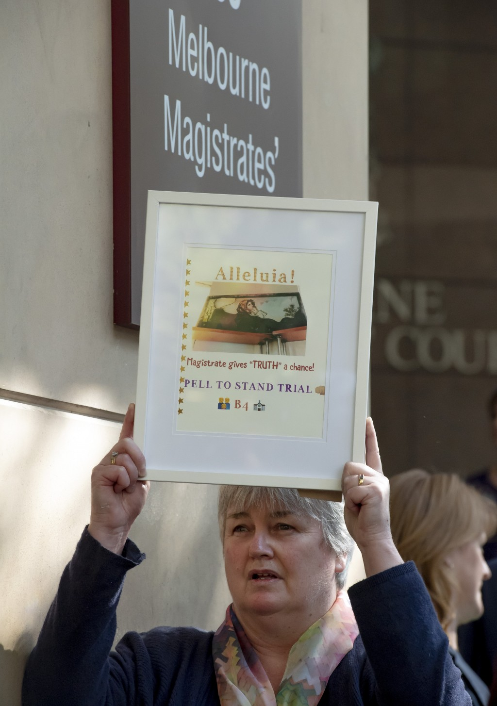 A demonstrator holds a placard outside the Melbourne Magistrate Court in Melbourne Tuesday, May 1, 2018. Australian Cardinal George Pell, the most sen...