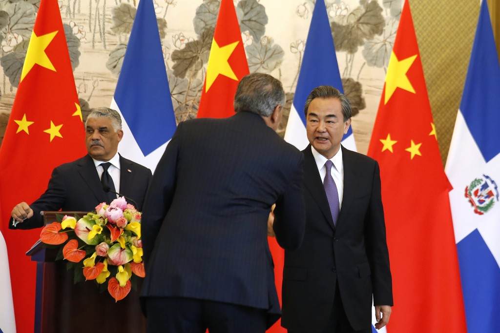 Chinese Foreign Minister Wang Yi, right, shakes hands with a Dominican Republic official after a press briefing with Dominican Foreign Minister Miguel...