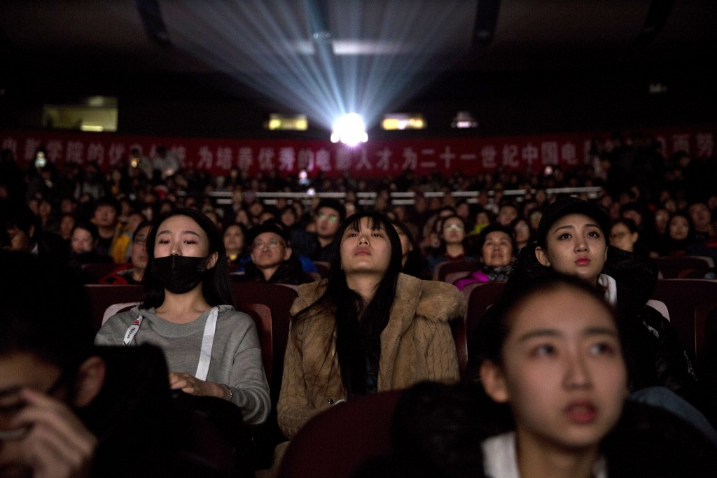 """In this Thursday, March 22, 2018 photo, audience members watch a screening of the state-backed documentary """"Amazing China"""" at the Beijing Film Academy..."""