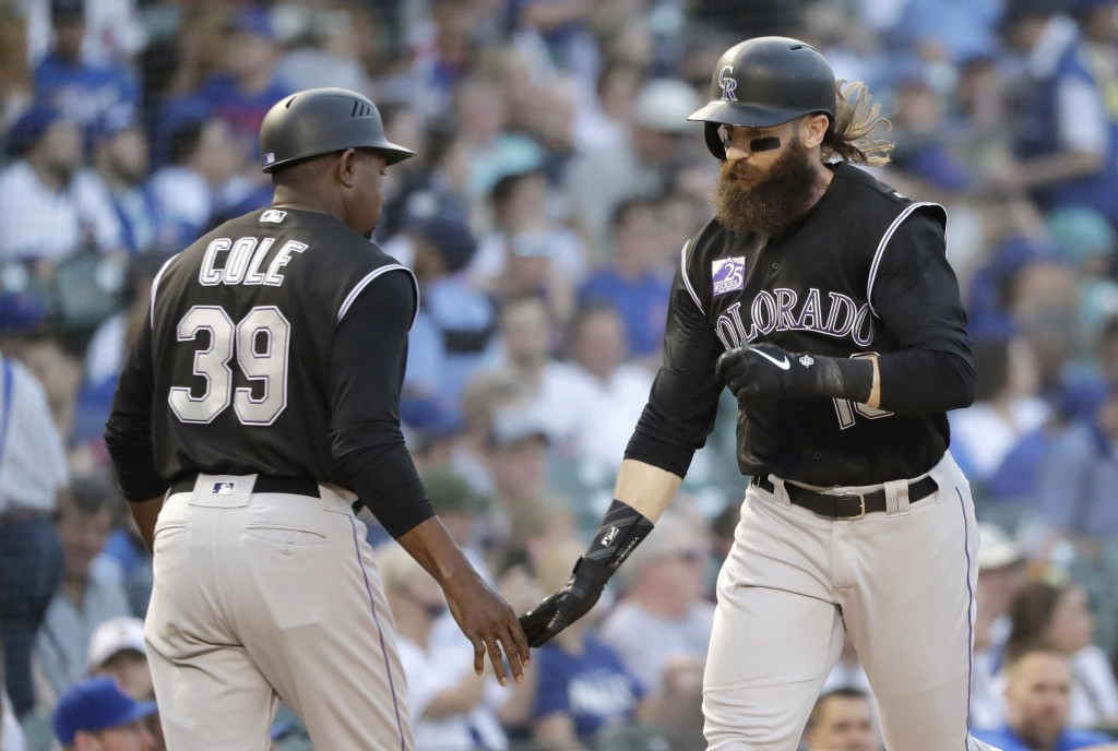 Colorado Rockies' Charlie Blackmon, right, celebrates his home run off Chicago Cubs starting pitcher Kyle Hendricks with third base coach Stu Cole dur...