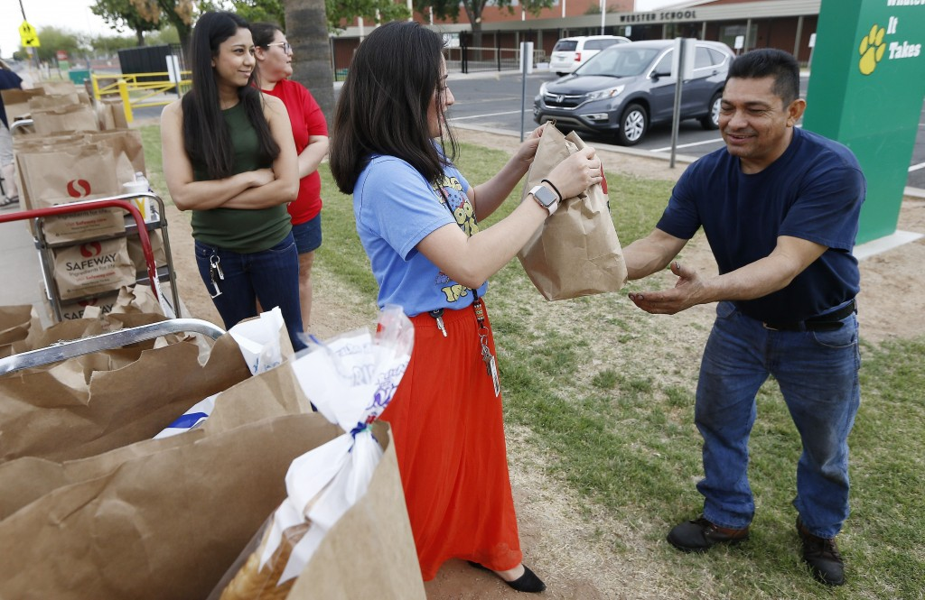 Erica Martinez, middle, a teacher at Webster Elementary School, hands out free food bags the teachers donated for their students and families as the s...