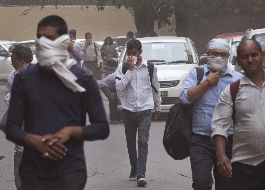 FILE - In this Wednesday, May 2, 2018 file photo, people cover their noses as a dust storm envelops the city in New Delhi, India. A powerful dust stor...