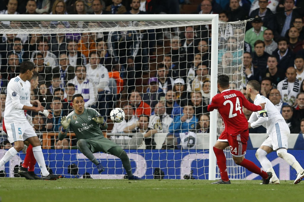Real Madrid's goalkeeper Keylor Navas, left, dives to save a shot by Bayern's Corentin Tolisso during the Champions League semifinal second leg soccer...