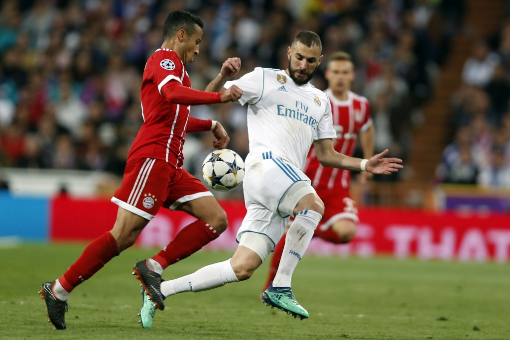 Bayern's Thiago, left, and Real Madrid's Karim Benzema challenge for the ball during the Champions League semifinal second leg soccer match between Re...