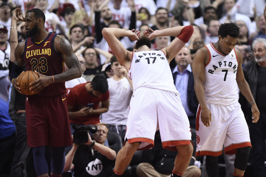 Toronto Raptors center Jonas Valanciunas (17) and guard Kyle Lowry (7) react after Valanciunas missed a shot late in the second half second, as Clevel...