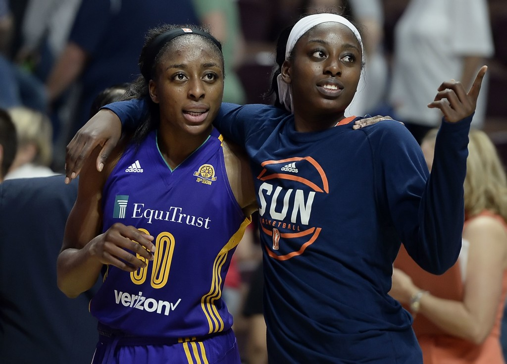FILE - In this May 26, 2016, file photo, sisters Los Angeles Sparks' Nneka Ogwumike, left, and Connecticut Sun's Chiney Ogwumike, right, walk off the ...