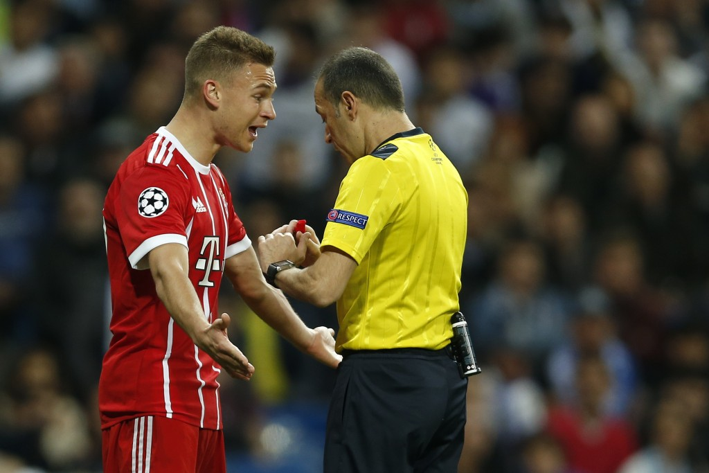 Bayern's Joshua Kimmich argues to Turkish referee Cuneyt Cakir during the Champions League semifinal second leg soccer match between Real Madrid and F...