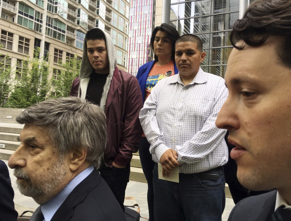 Daniel Ramirez Medina, center right in light-colored shirt, listens as two of his lawyers, Mark Rosenbaum, left, and Nathaniel Bach, right, address re...