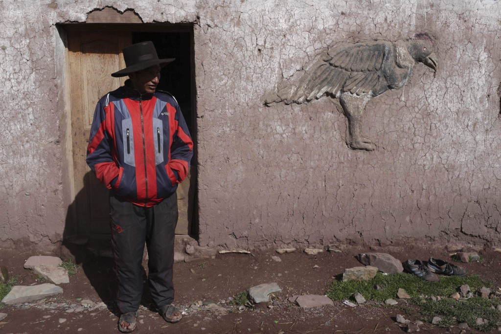 In this March 2, 2018 photo, Miguel Rocco stands in front of his home in Pitumarca, Peru. The local indigenous community has struggled with high rates...