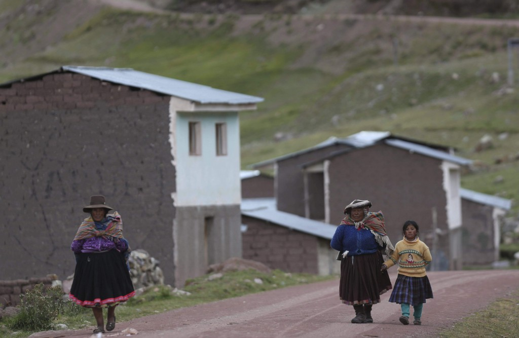 In this April 4, 2018 photo, women walk near to the route to the recently-discovered mountain dubbed Rainbow Mountain, in Pitumarca, Peru. The flood o...