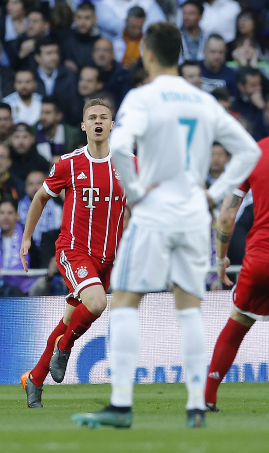 Real Madrid's Cristiano Ronaldo, right, looks on as Bayern's Joshua Kimmich celebrates after scoring the opening goal during the Champions League semi...