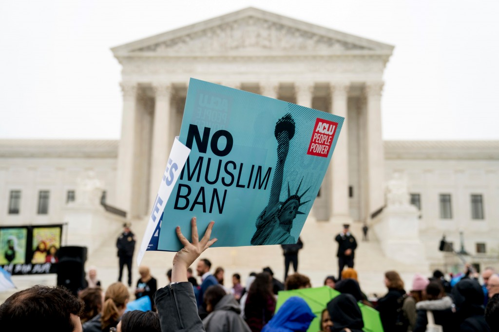 """FILE - In this April 25, 2018 file photo, a person holds up a sign that reads """"No Muslim Ban"""" during an anti-Muslim ban rally as the Supreme Court hea..."""