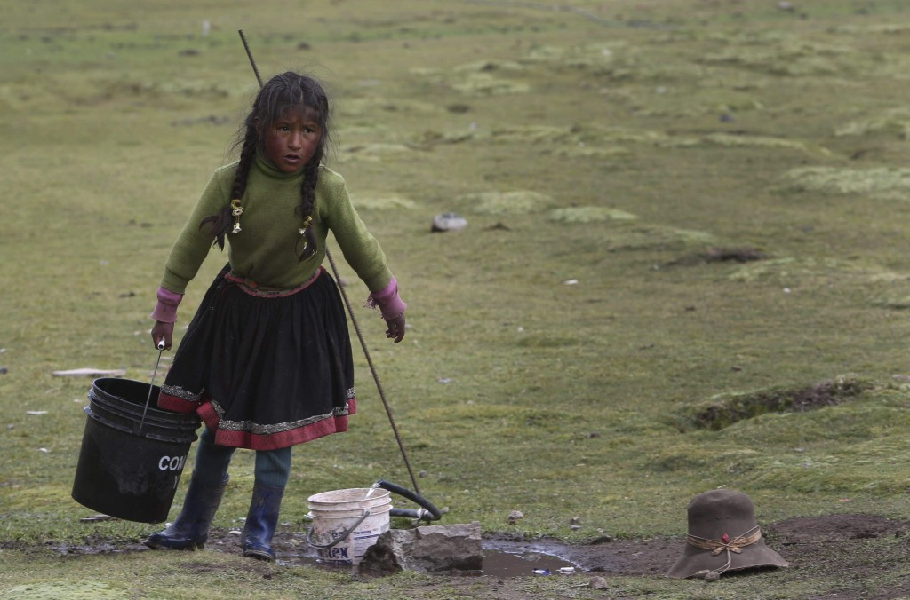 In this March 2, 2018 photo, a child hauls a bucket of water in Pitumarca, Peru, near Rain Mountain. The popularity of Rainbow Mountain, which attract...