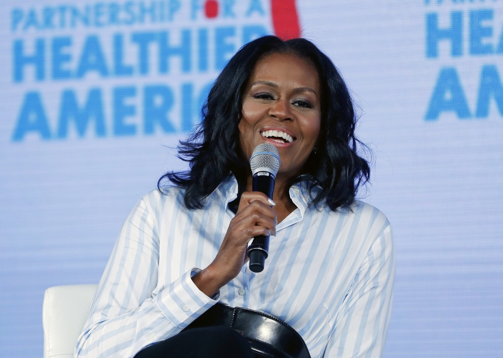 FILE - In this May 12, 2017, file photo, former first lady Michelle Obama smiles while speaking at the Partnership for a Healthier American 2017 Healt...