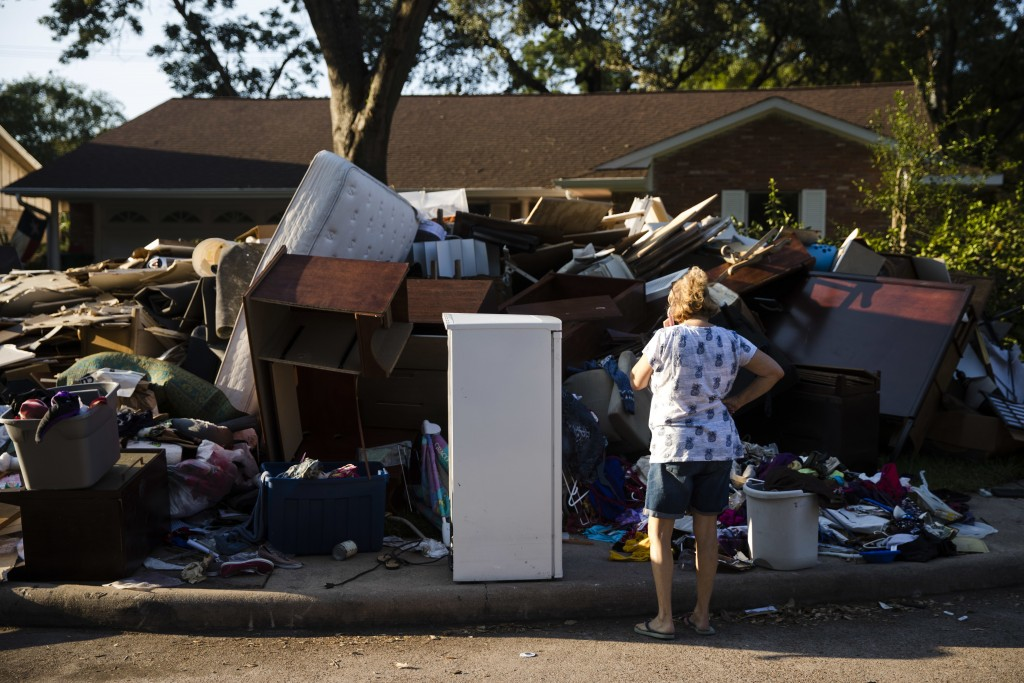 FILE - In this Sept. 6, 2017, file photo, a resident looks at debris piled in front of her home in the aftermath of Hurricane Harvey in Houston. Offic...