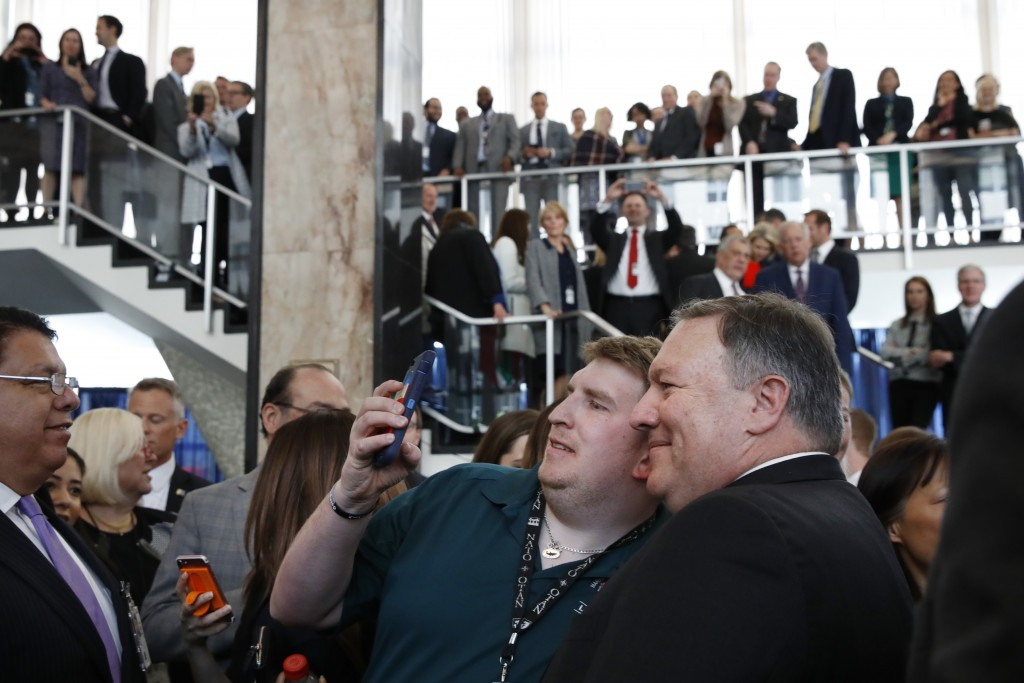 New Secretary of State Mike Pompeo, right, takes selfies with State Department employees after a speaking to the group on arrival at the State Departm...