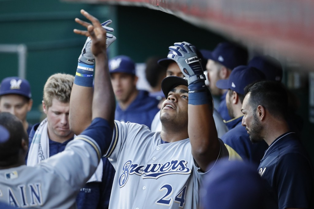 Milwaukee Brewers' Jesus Aguilar celebrates in the dugout after hitting a solo home run off Cincinnati Reds starting pitcher Homer Bailey during the f...