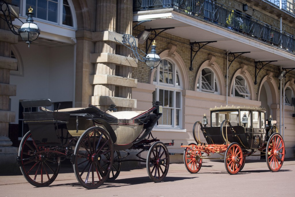 The Ascot Landau open carriage, left, which will be used in the case of dry weather, stands with the Scottish State Carriage, to be used in the case o...