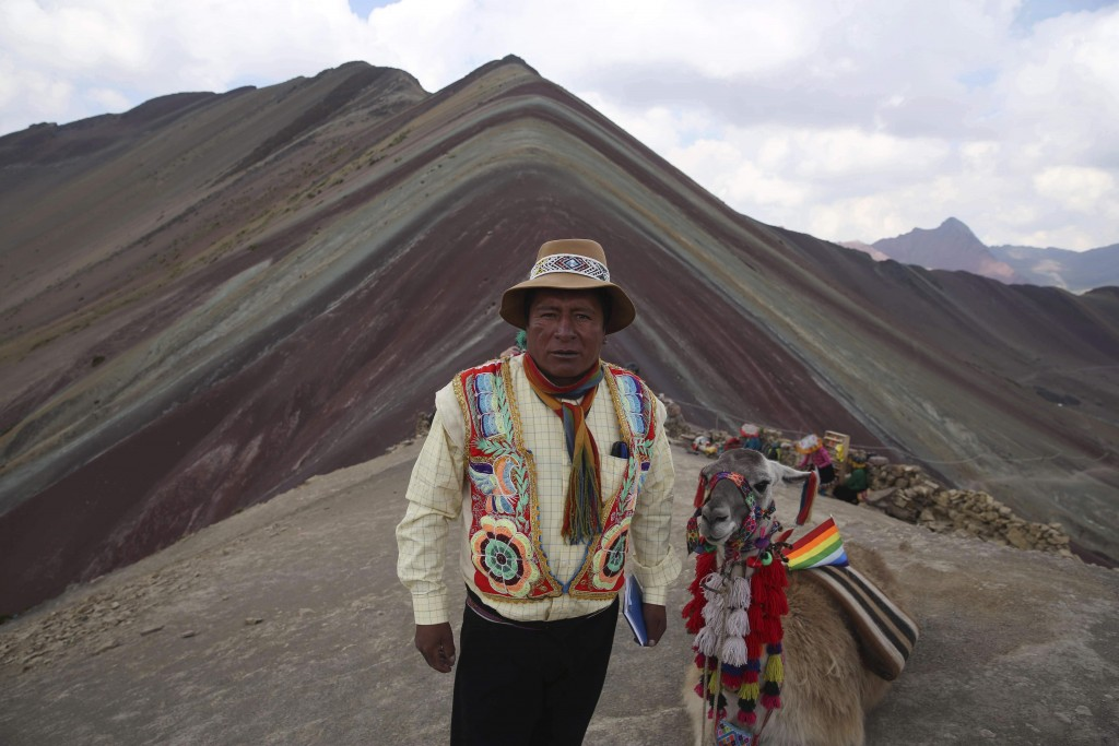 In this April 5, 2018 photo, community leader Gabino Human poses for a photo backdropped by Rainbow Mountain, in Pitumarca, Peru. A surge in tourists ...