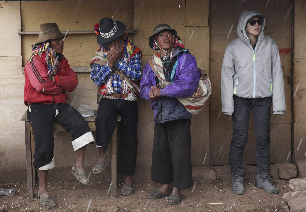 In this April 5, 2018 photo, Andean muleteers and a tourist take cover from a rain shower during a tour to Rainbow Mountain, in Pitumarca, Peru. Backp...