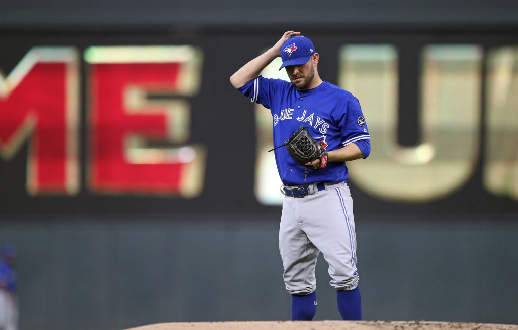 Toronto Blue Jays' pitcher Marco Estrada waits after giving up a solo home run to Minnesota Twins' Joe Mauer during the first inning of a baseball gam...