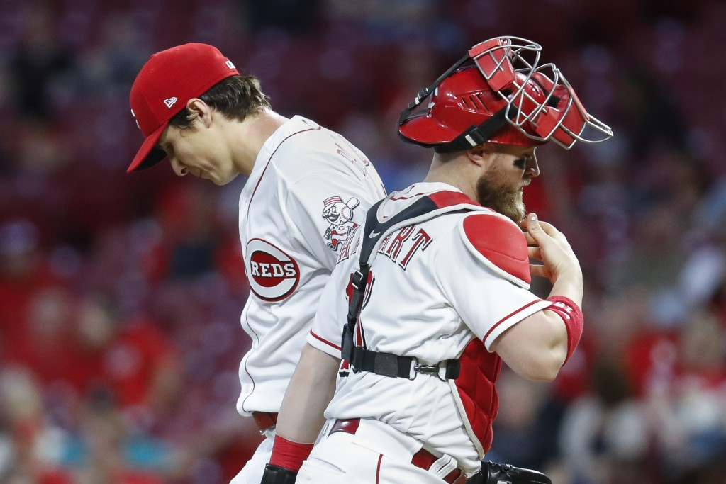 Cincinnati Reds starting pitcher Homer Bailey, left, meets with catcher Tucker Barnhart, right, during the fifth inning of a baseball game against the...