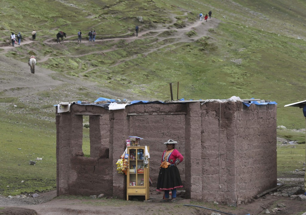 In this March 2, 2018 photo, an Andean woman sell candies, water and chips, on the route to Rainbow Mountain, in Pitumarca, Peru. The popularity of Ra...