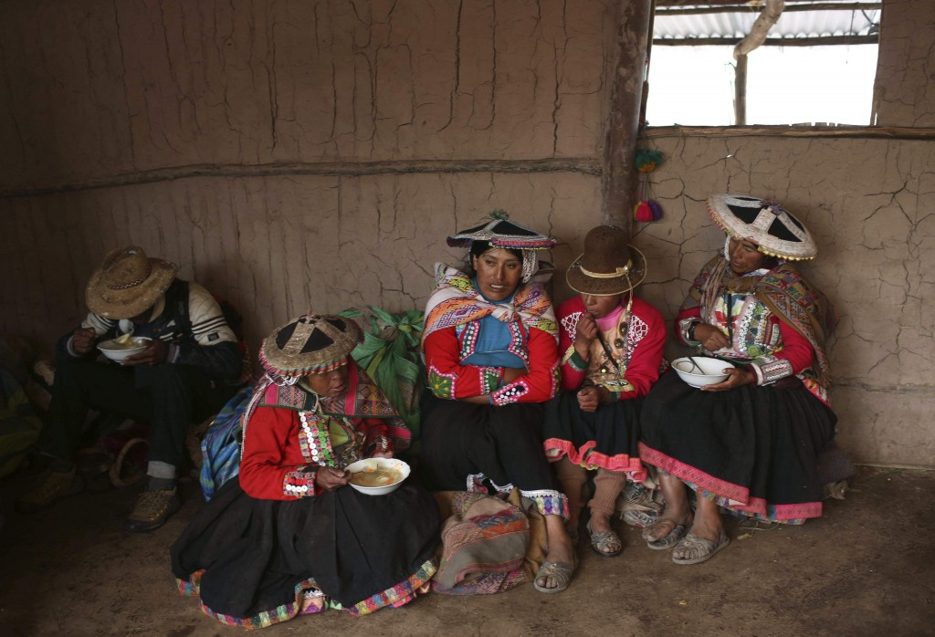 In this April 5, 2018 photo, a group of Andean muleteers break for lunch during a tour guide to Rainbow Mountain, in Pitumarca, Peru. Roughly 500 vill...