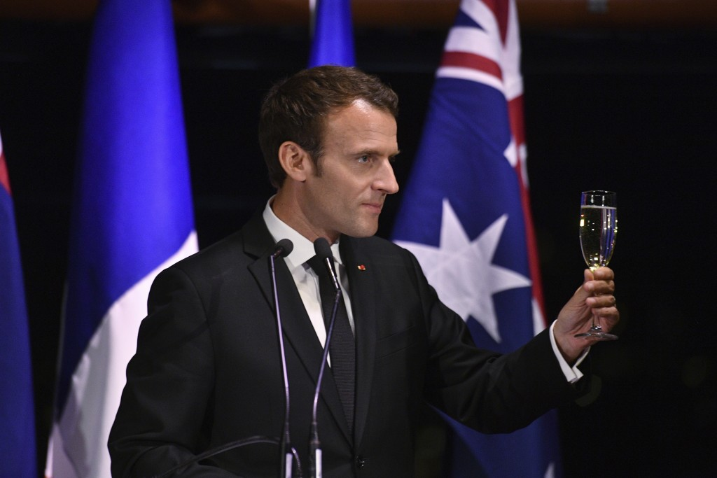 President of France, Emmanuel Macron, holds up his glass during a dinner hosted by and Australian Prime Minister, Malcolm Turnbull, at the Sydney Oper...