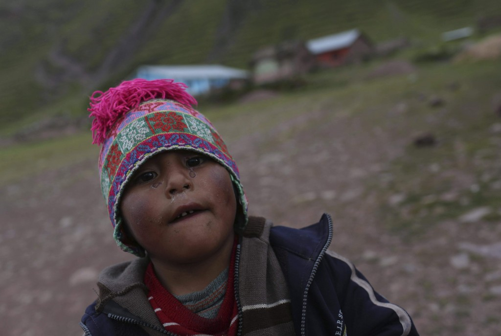 In this April 4, 2018 photo, Henry, 5 years old, eyes the camera outside his school in Pitumarca, Peru, near Rainbow Mountain. Environmentalists fear ...