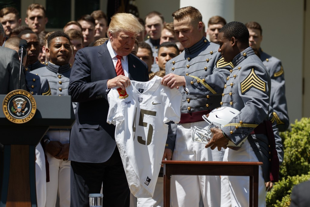 President Donald Trump is presented with a jersey by Ahmad Bradshaw, right, and John Voit, center, during a ceremony to present the Commander in Chief...