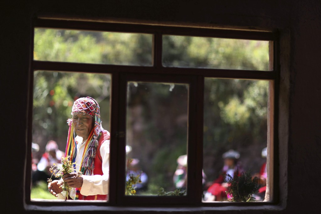 In this April 4, 2018 photo, a farmer who now sells Andean clothes collects flowers while he waits for tourists who have come to see Rainbow Mountain,...