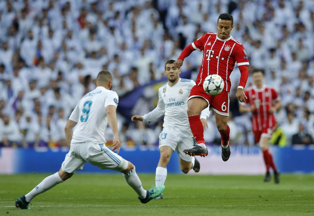 Real Madrid's Karim Benzema, left, looks on as Bayern's Thiago controls a ball during the Champions League semifinal second leg soccer match between R...