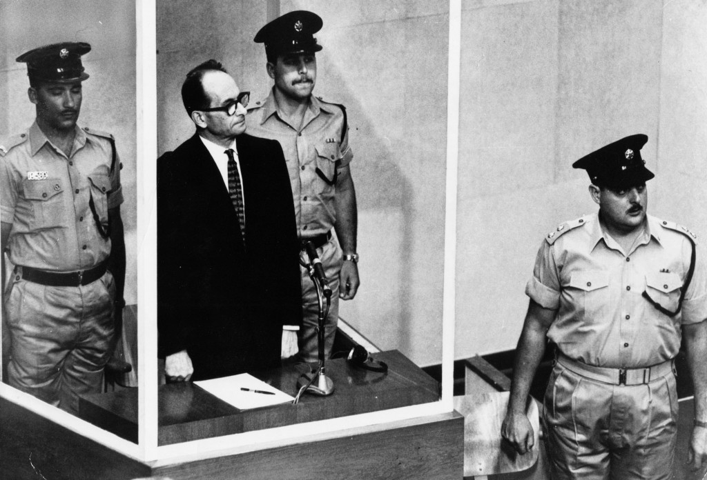 FILE - The 1961 file photo shows Adolf Eichmann standing in his glass cage, flanked by guards, in the Jerusalem courtroom during his trial in 1961 for...