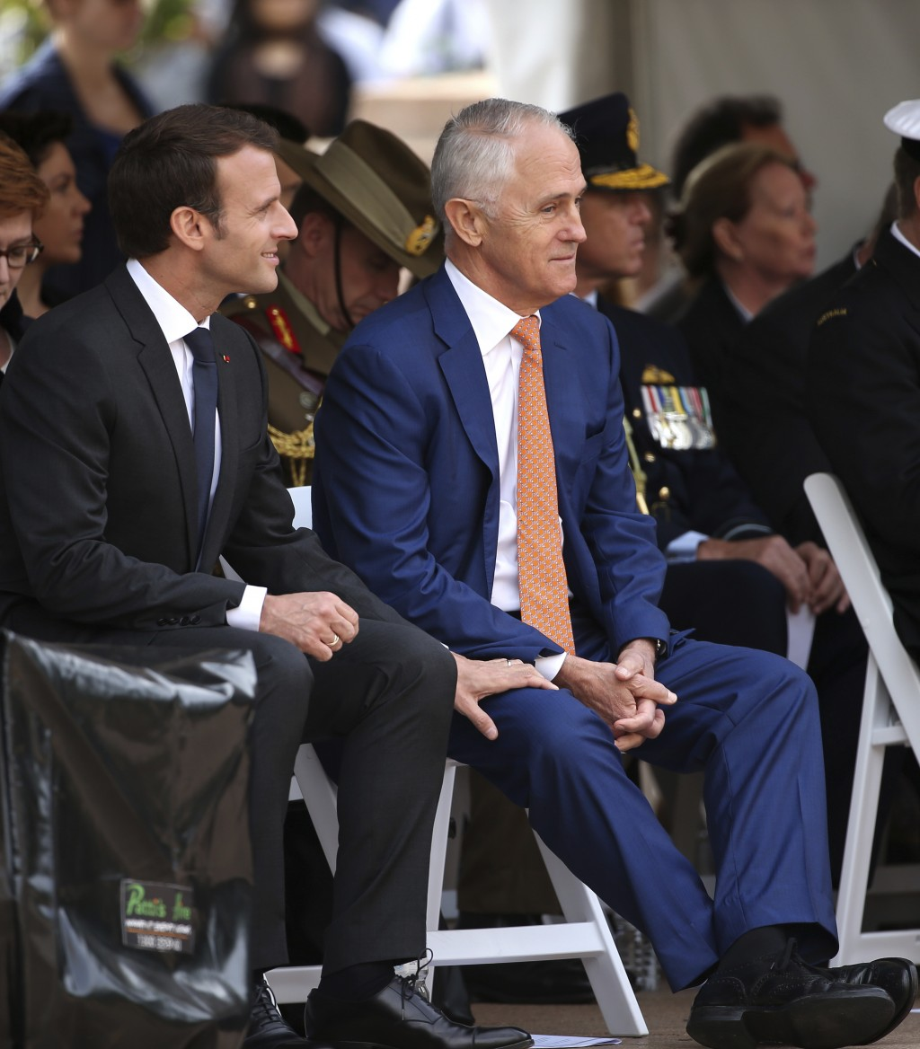 French President Emmanuel Macron, left, grips the leg of Australian Prime Minister Malcolm Turnbull during a war commemorative ceremony in Sydney, Wed...