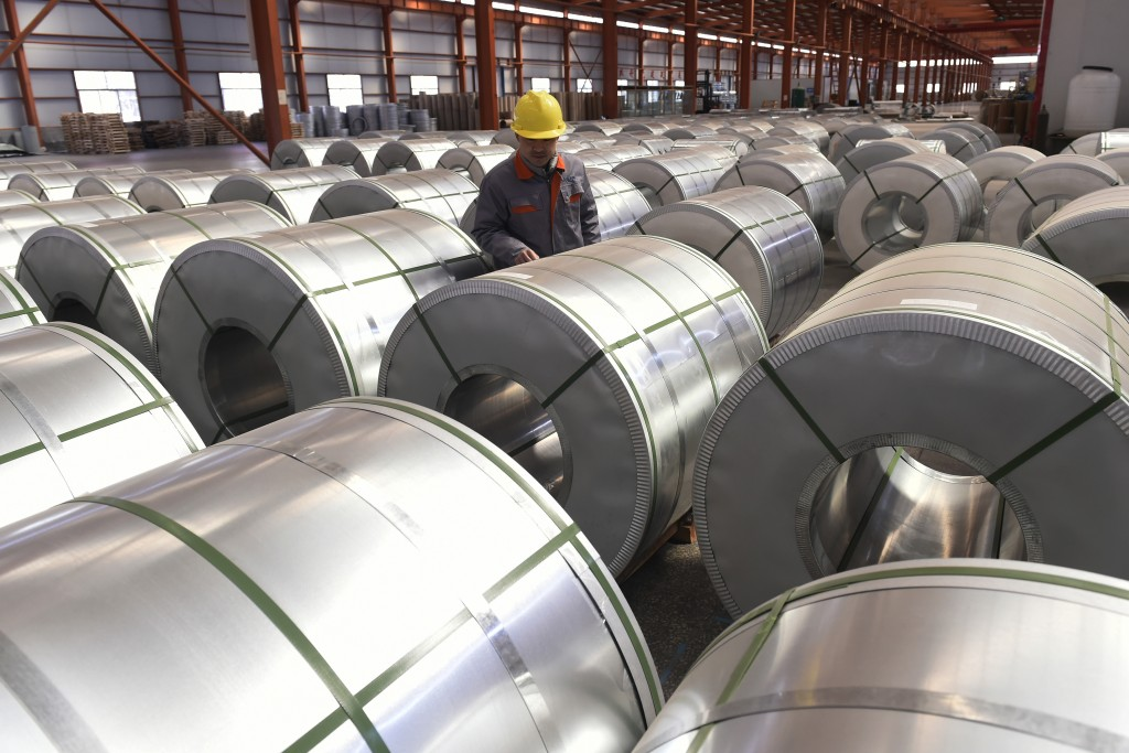 FILE - In this April 7, 2018, file photo, a worker checks on rolls of aluminum at a factory in Zouping county in east China's Shandong province. Small...