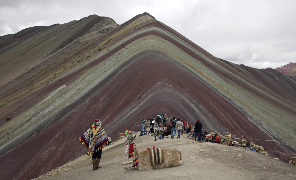 In this March 2, 2018 photo, an Andean man rests with his llama on Rainbow Mountain in Pitumarca, Peru. Tourists gasp for breath as they climb for two...