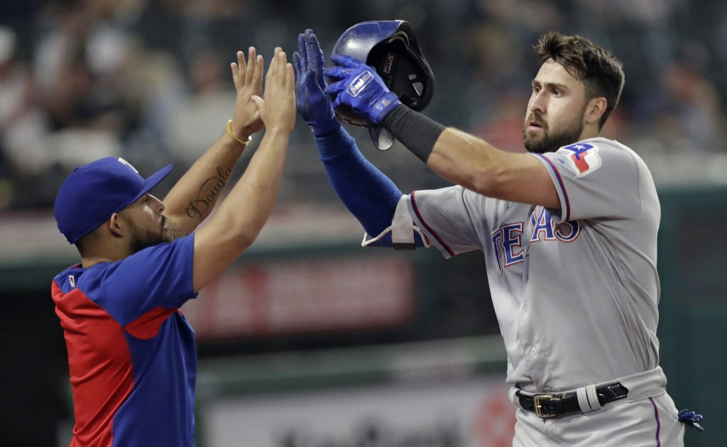Texas Rangers' Rougned Odor, left congratulates Joey Gallo after Gallo hit a solo home run in the 12th inning of a baseball game against the Cleveland...