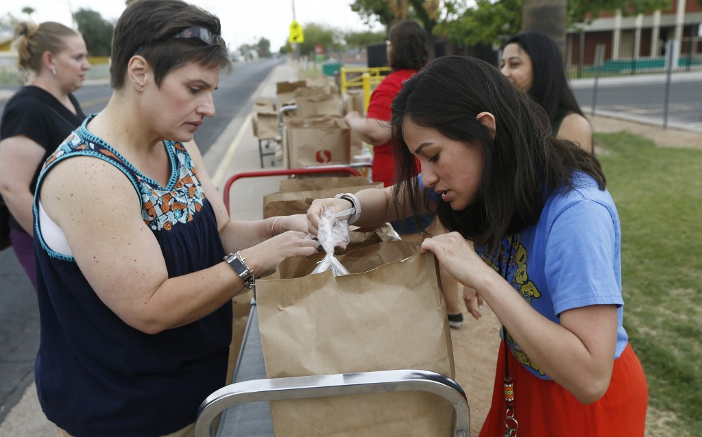 Librarian Elaine Cecil, left, and teacher Erica Martinez, right, at Webster Elementary School, checks the contents of free food bags they donated for ...
