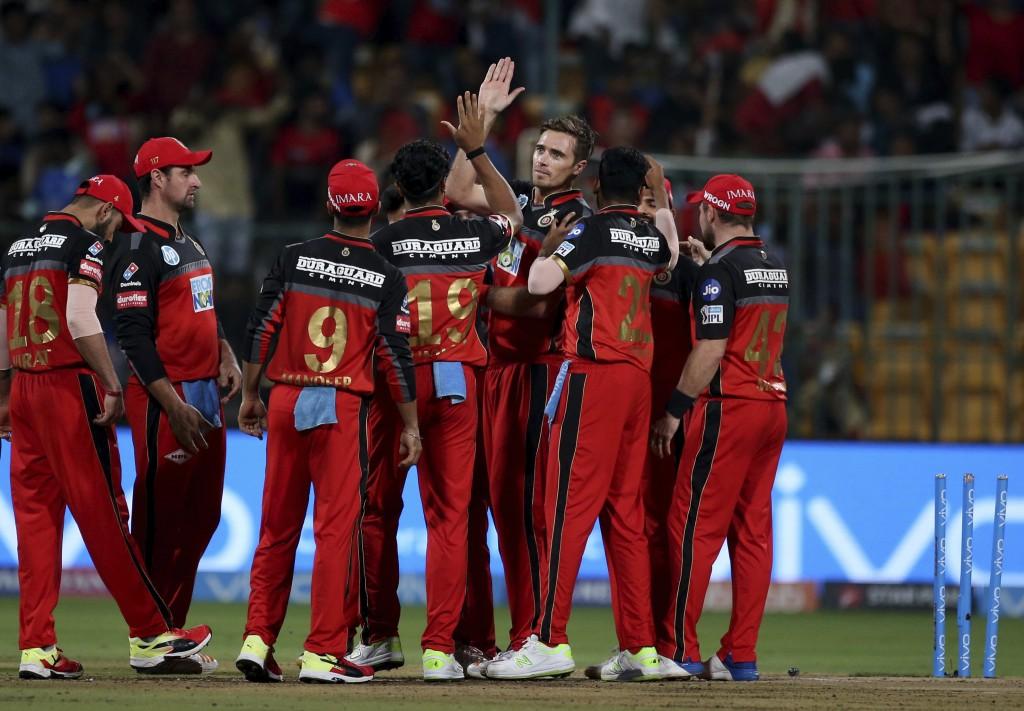 Royal Challengers Bangalore's Tim Southee, facing camera without cap, celebrates with teammates the dismissal of Mumbai Indians' Ishan Kishan during t...