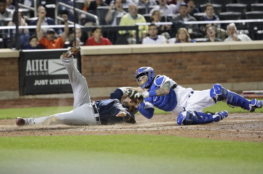 New York Mets catcher Tomas Nido tags out Atlanta Braves' Kurt Suzuki at home plate during the seventh inning of a baseball game Tuesday, May 1, 2018,...
