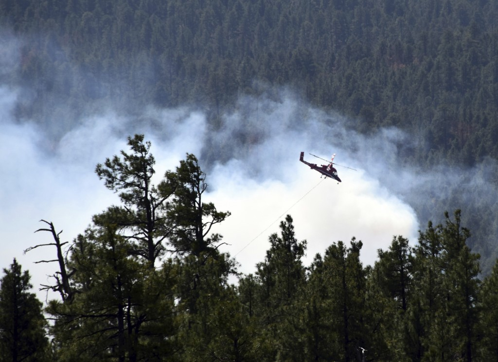 This April 30, 2018 photo provided by the U.S. Forest Service shows a helicopter fighting a wildfire in north-central Arizona. Fire officials say high...