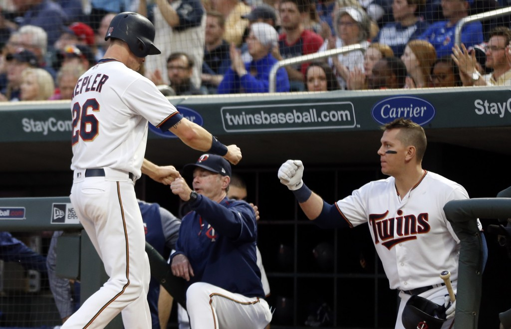 Minnesota Twins' Max Kepler, left, is congratulated by manager Paul Molitor and Logan Morrison, right, after scoring on a double by Eddie Rosario off ...