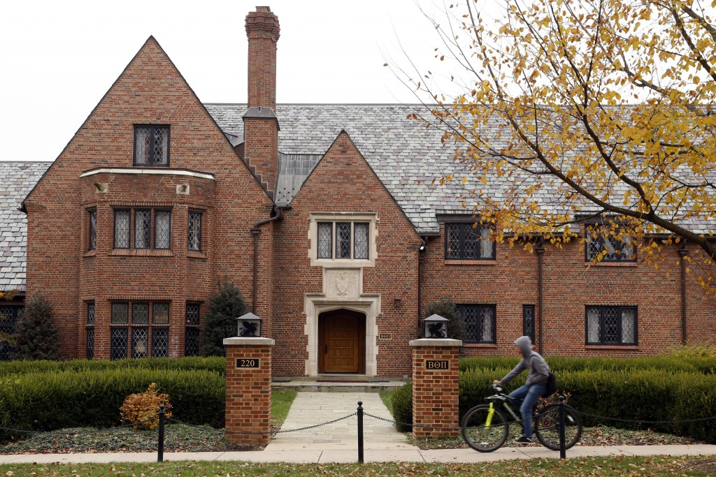 FILE – In this Nov. 9, 2017, file photo, a bicyclist rides past Pennsylvania State University's shuttered Beta Theta Pi fraternity house in State Coll...