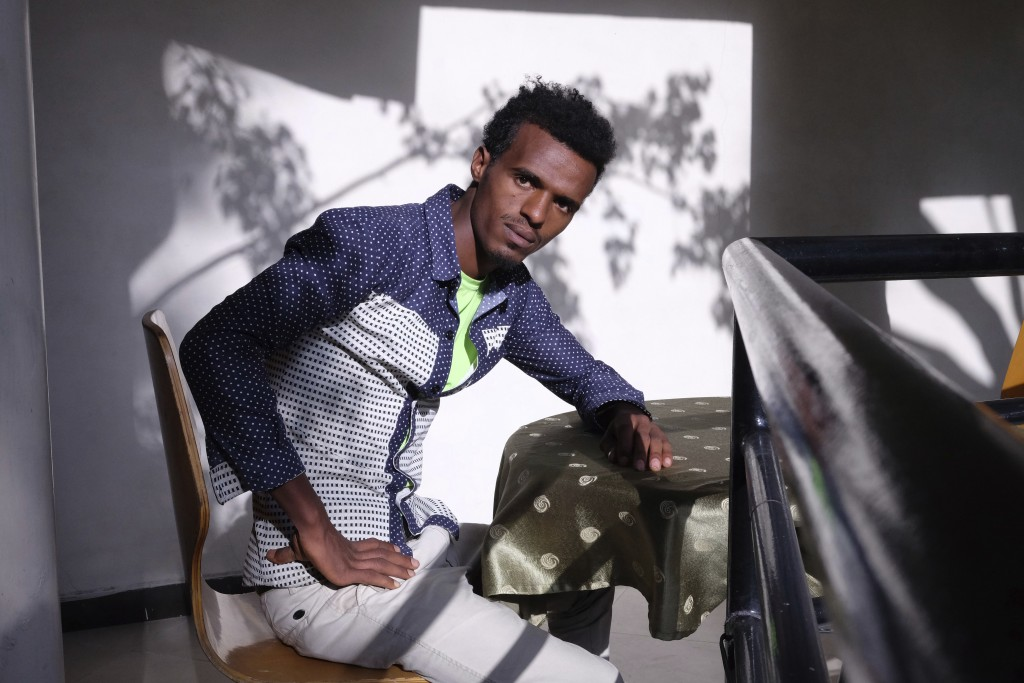 In this March 21, 2018 photo, Getahun Alemu, 20, a former employee of Huajian, poses for a photo in Dukem, Ethiopia, near Addis Ababa. Alemu, who quit...