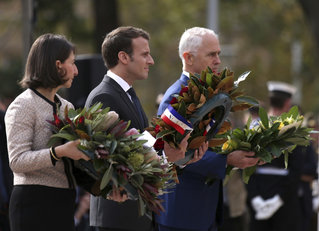 French President Emmanuel Macron, center, Australian Prime Minister Malcolm Turnbull, right, and New South Wales state Premier Gladys Berejiklian plac...