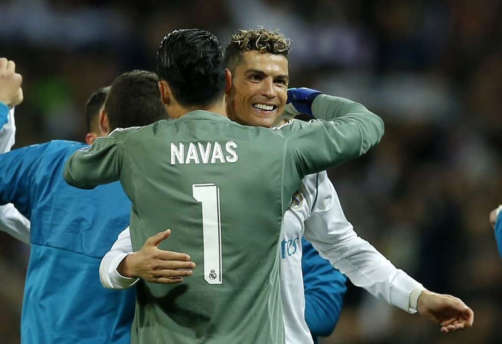 Real Madrid's goalkeeper Keylor Navas, left, hugs his teammate Cristiano Ronaldo, right, after advancing to the final when playing 2-2 during the Cham...